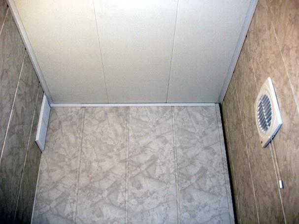 De bekleding van het toilet op het kunststof profiel van het paneel ...